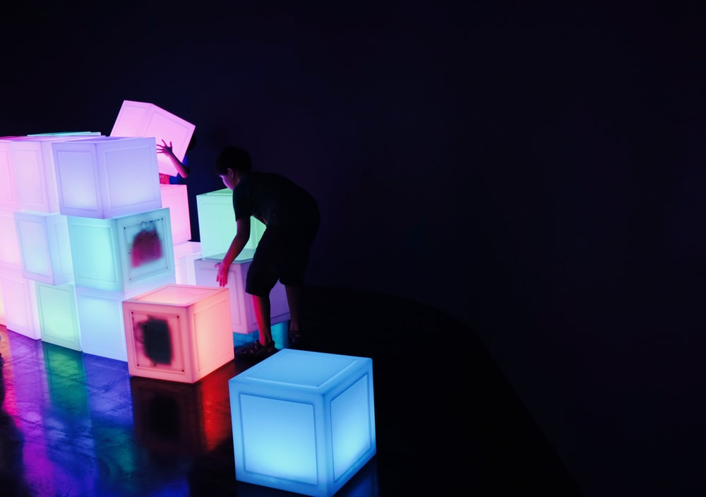 man in black t-shirt standing beside pink and blue led light