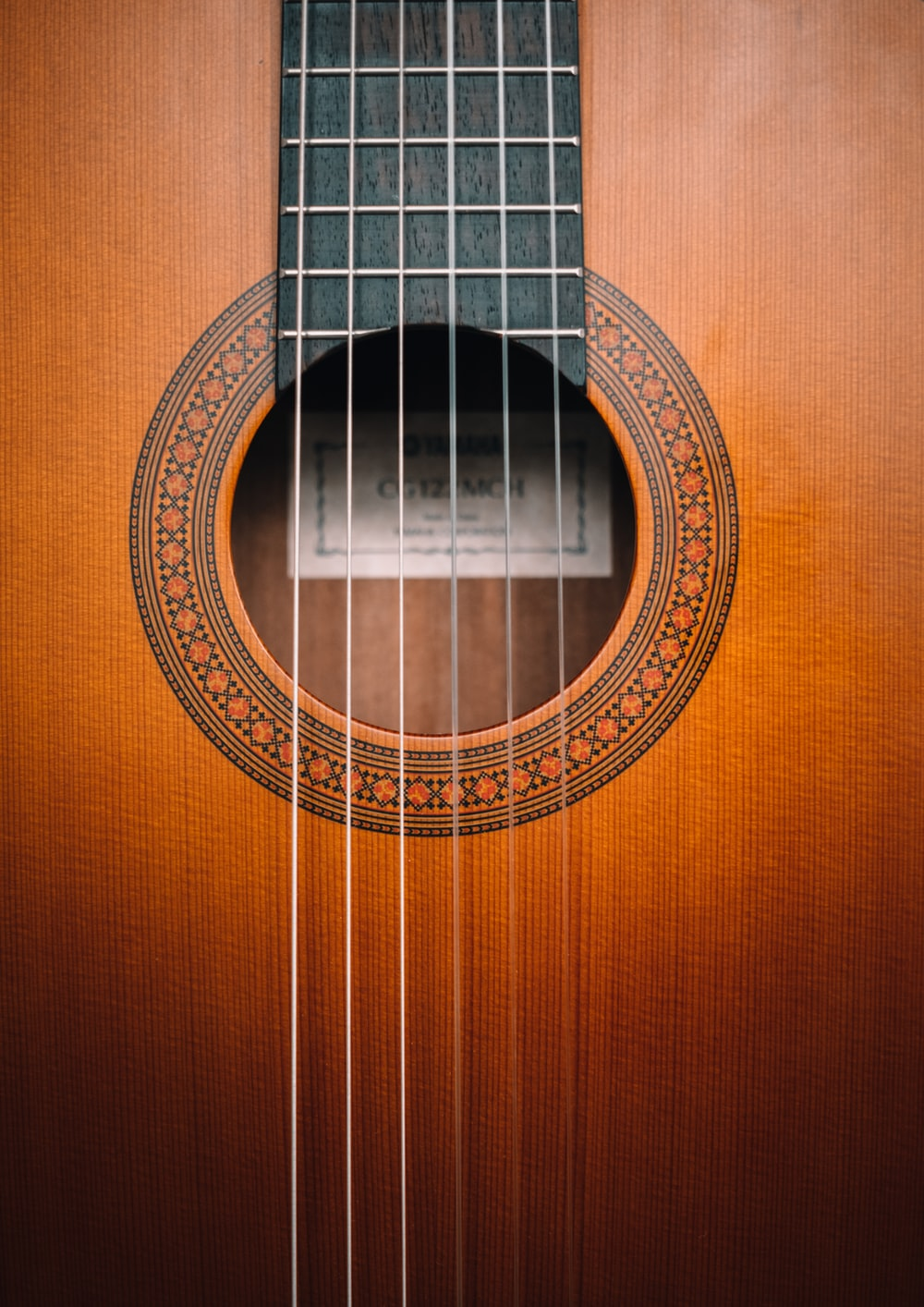 brown acoustic guitar on brown wooden surface