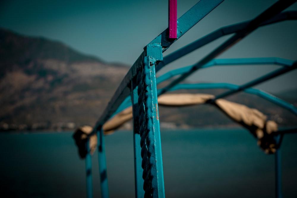 blue metal railings near body of water during daytime