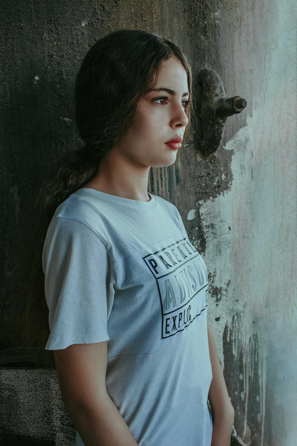 woman in gray crew neck t-shirt standing beside gray concrete wall