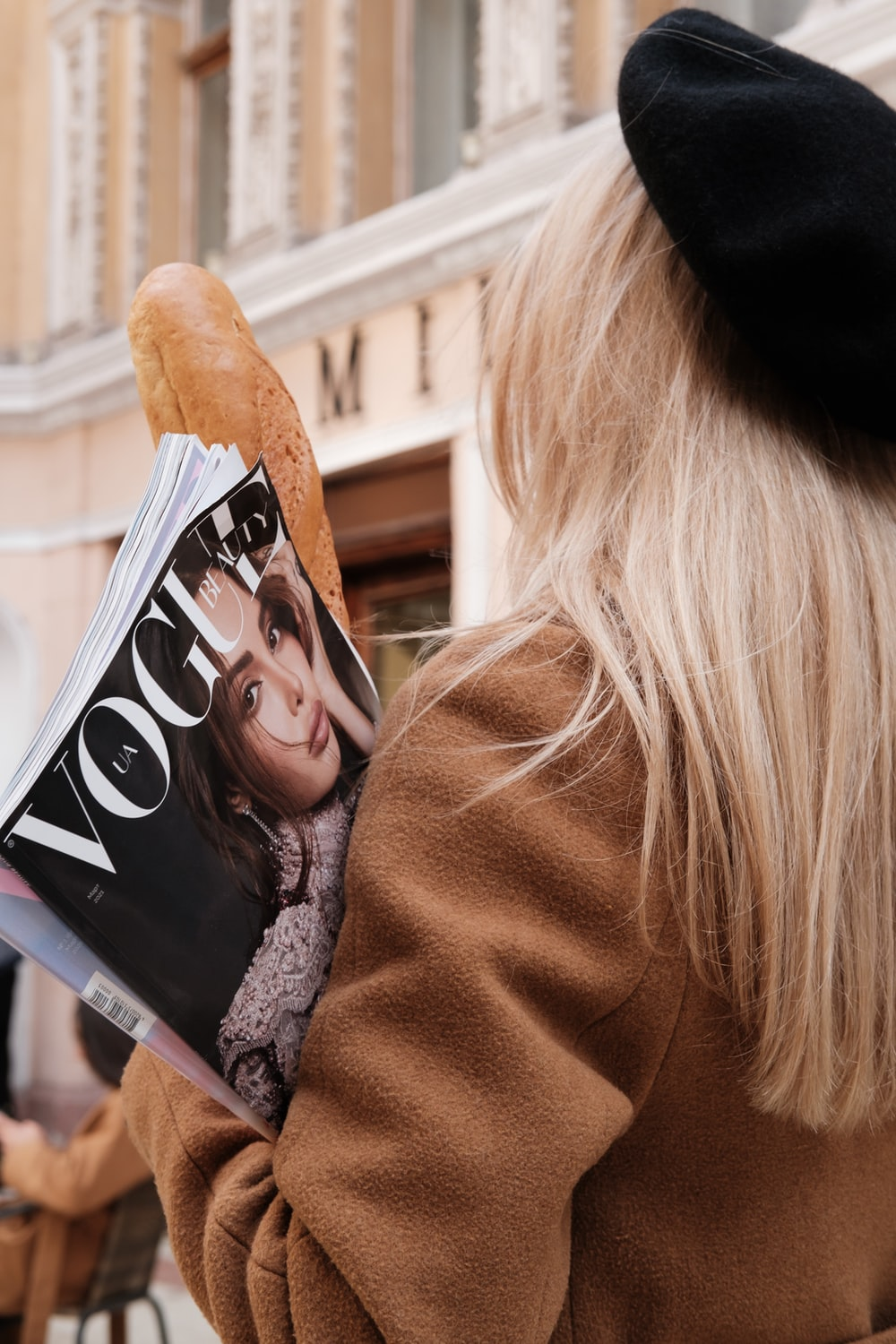 woman in brown coat holding magazine