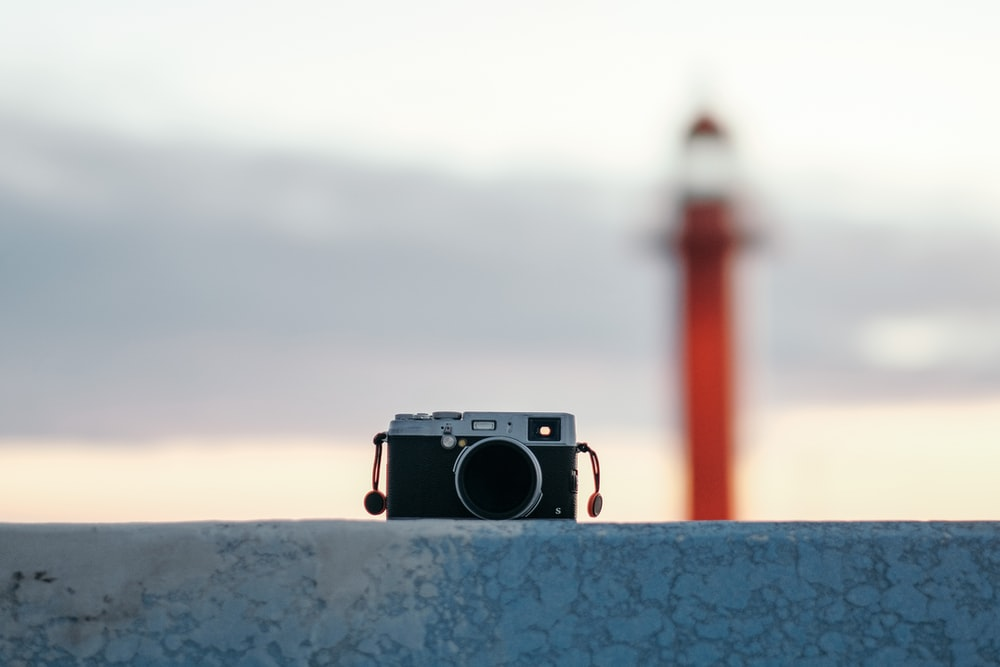 black and silver camera on blue concrete wall