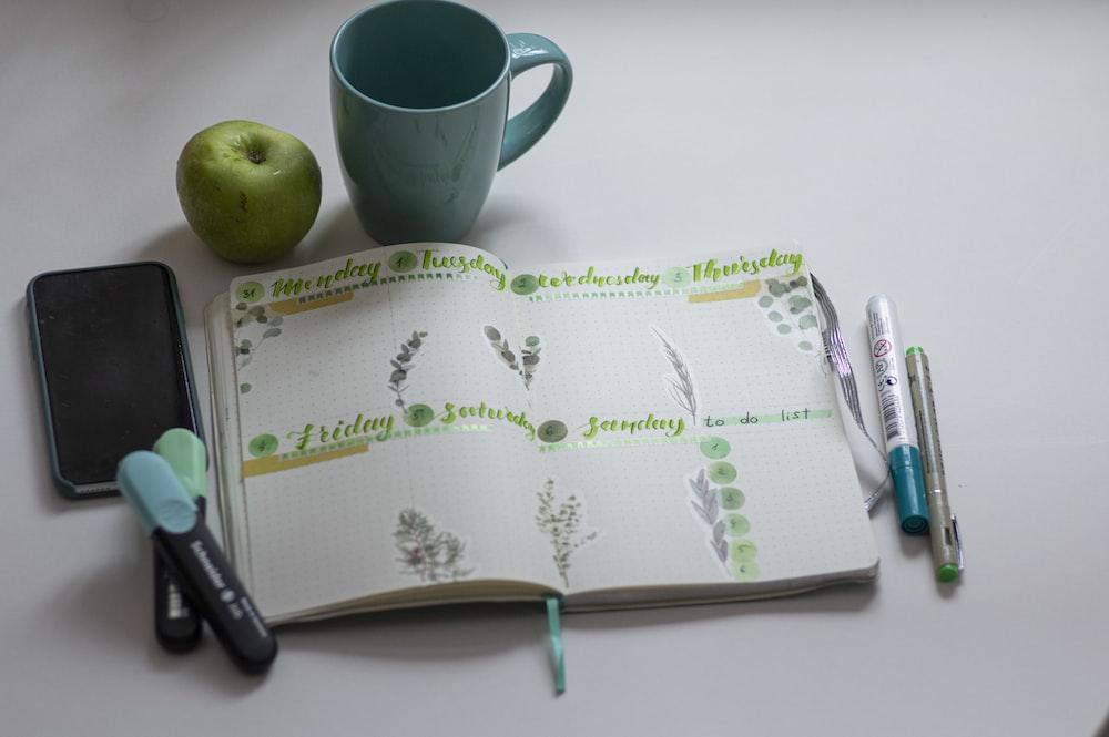 green ceramic mug beside black click pen on white and green book