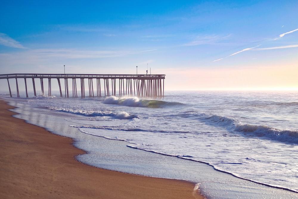 sea waves crashing on beach shore during daytime