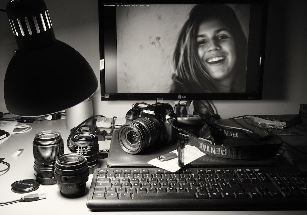 black flat screen computer monitor beside black dslr camera