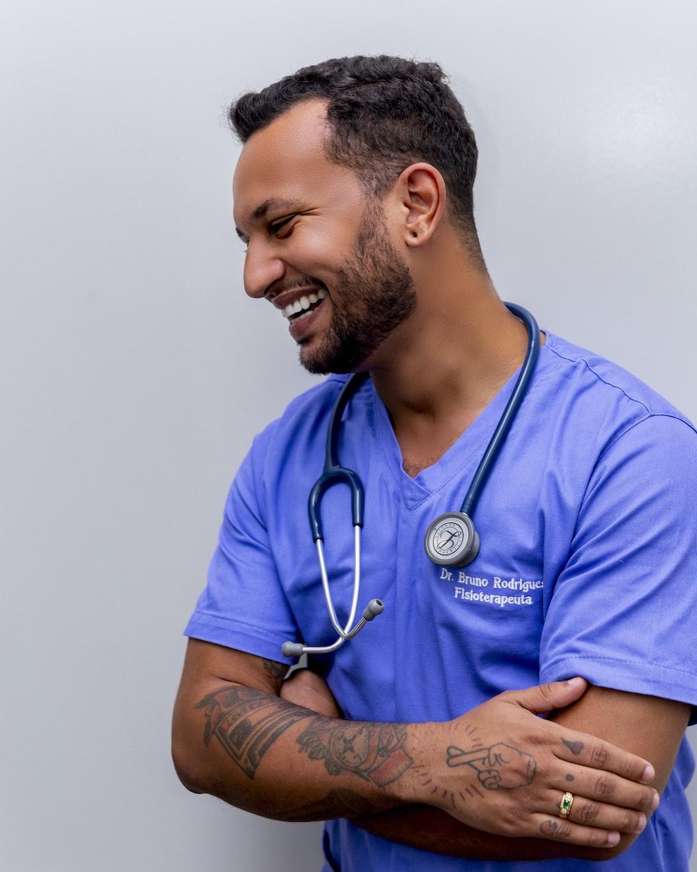 man in blue scrub suit wearing blue stethoscope