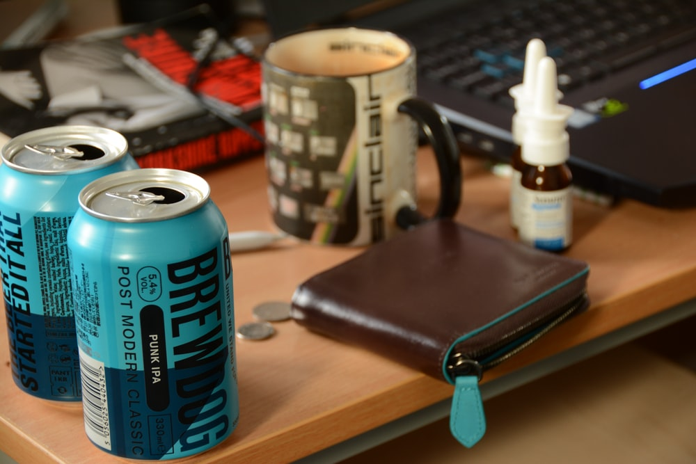 blue can beside black leather wallet on brown wooden table
