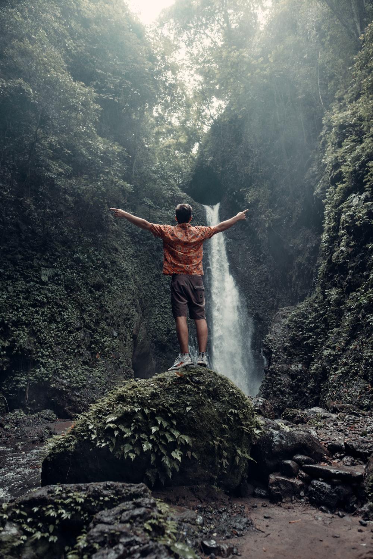 man in orange shirt standing on rock near waterfalls during daytime