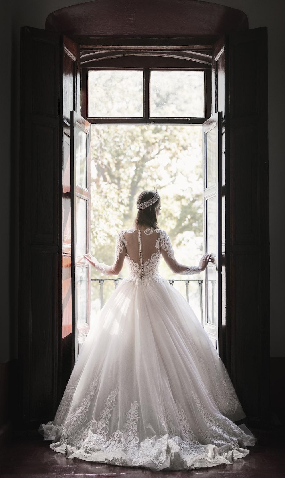 woman in white wedding dress standing near window during daytime