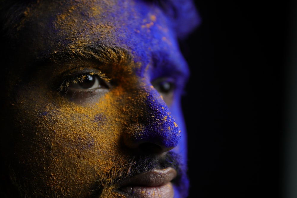 man with purple and blue powder on face