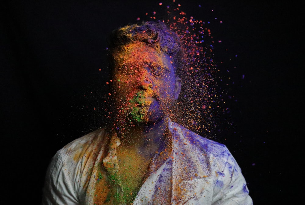man in white shirt with green and blue powder on his face