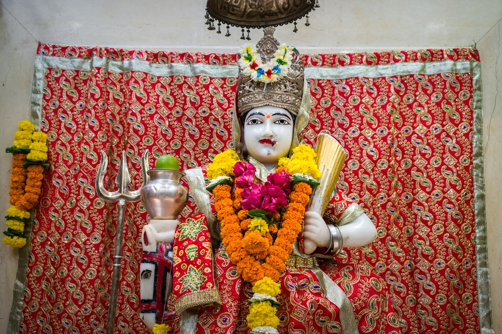 woman in red and gold sari dress holding white ceramic mug