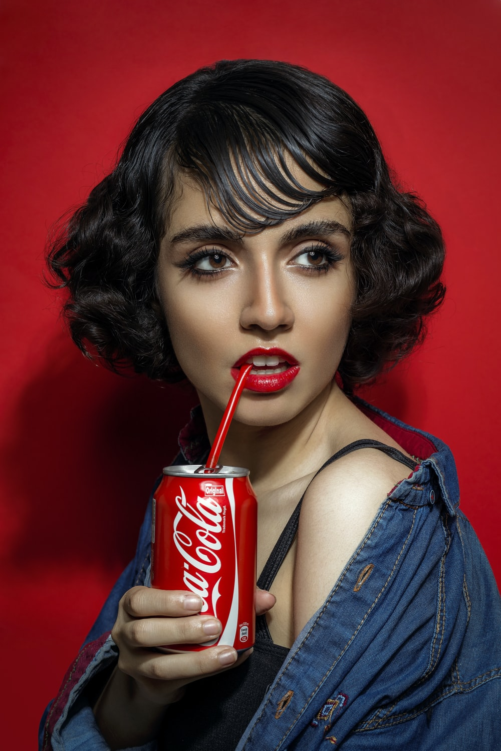 woman in blue tank top holding coca cola can