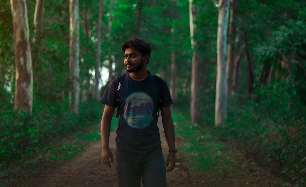 man in blue crew neck t-shirt standing on forest during daytime
