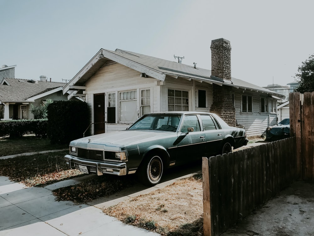 black sedan parked beside brown wooden fence