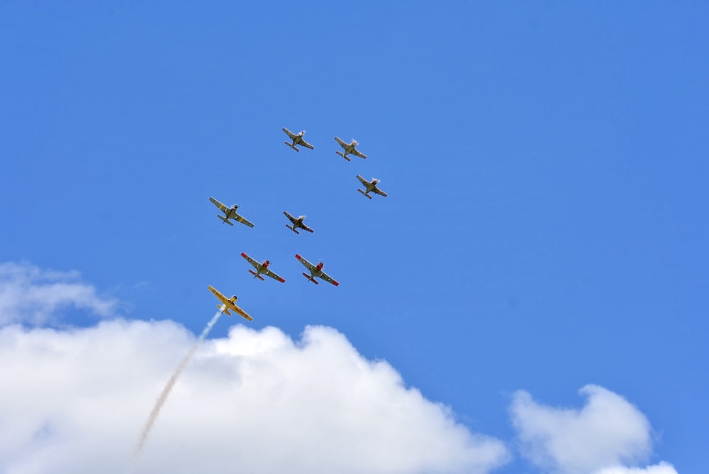 four fighter planes in mid air under blue sky during daytime