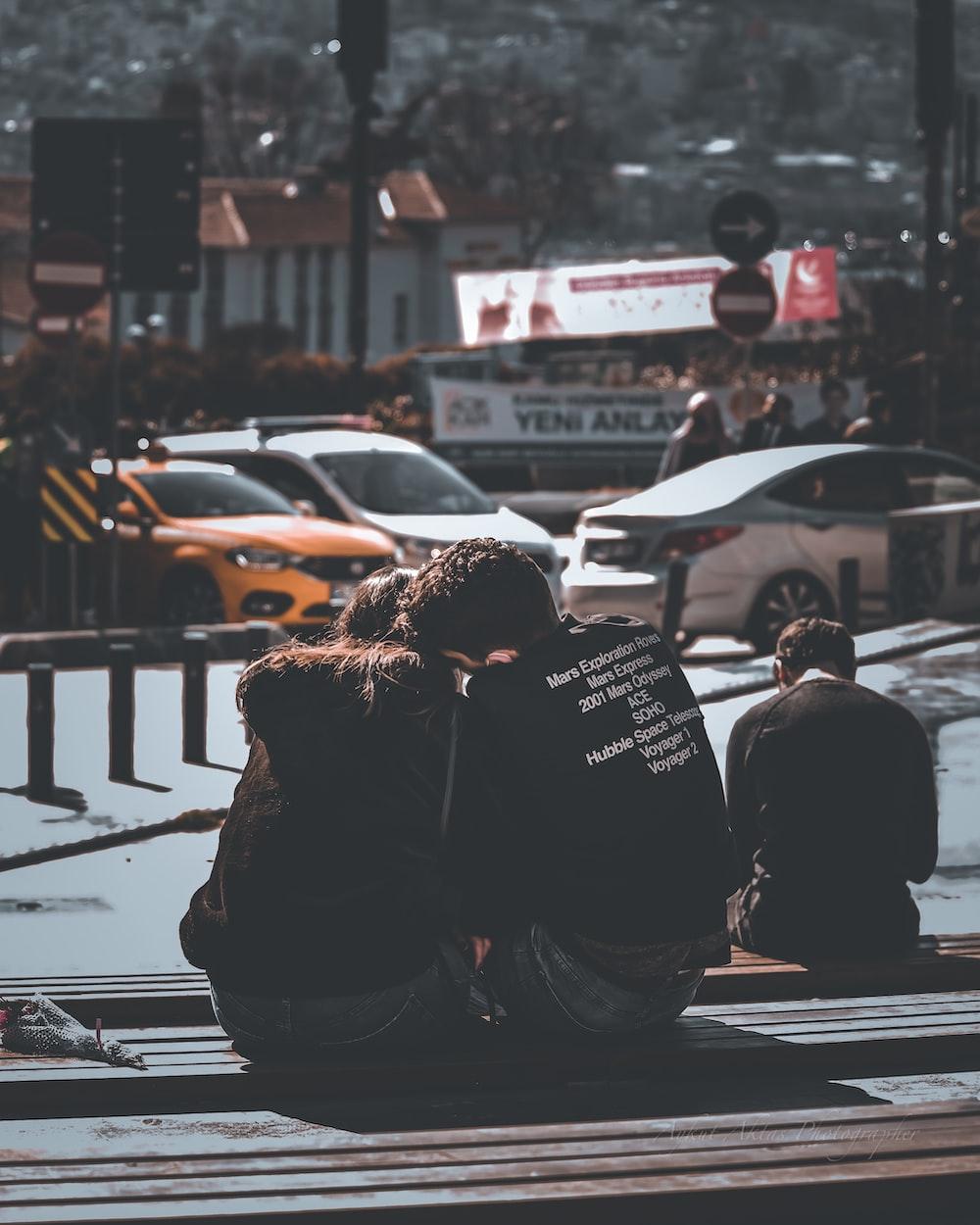 man and woman sitting on sidewalk during daytime