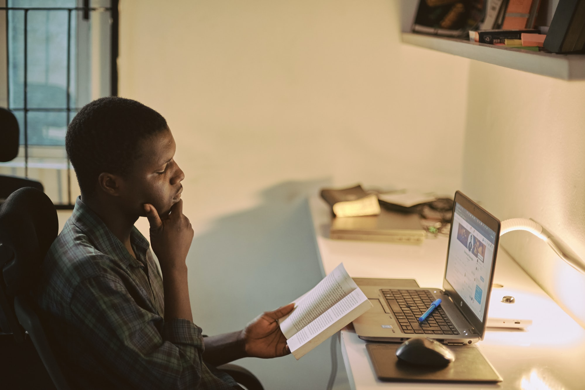 Portrait of a creative African man taking a break from work to read with his workspace blurred in the background