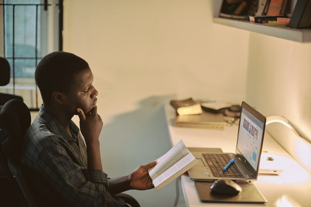 Young man reading a book with an open laptop in front of him