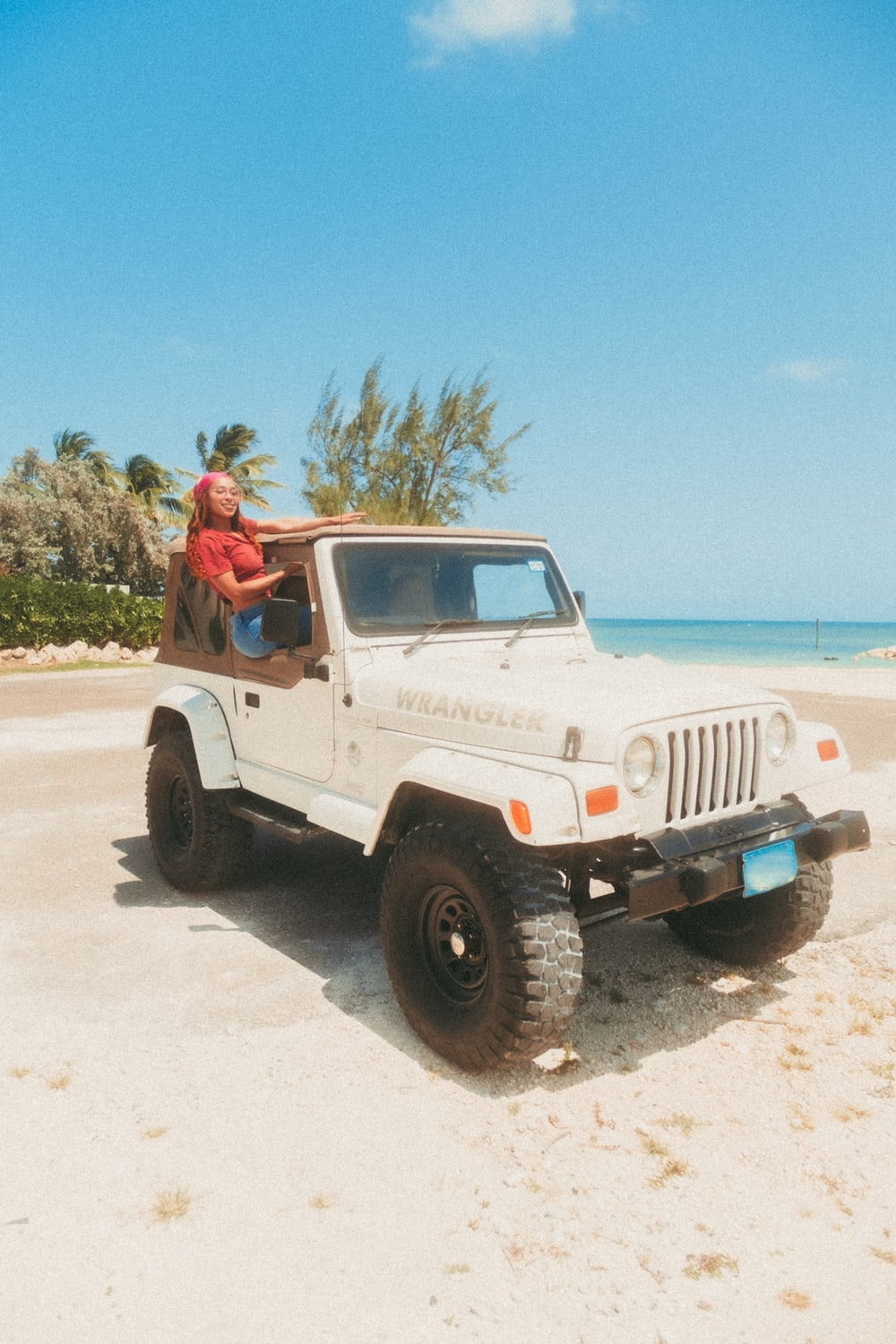 man in brown shirt sitting on white jeep wrangler on beach during daytime