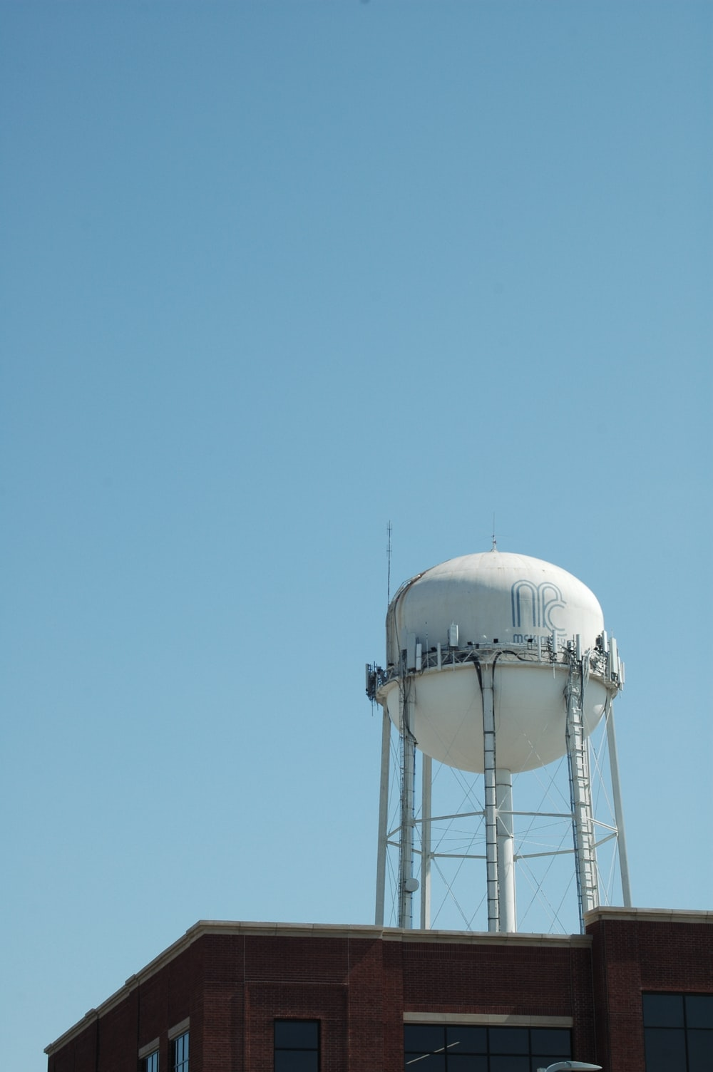 white and gray water tank under blue sky during daytime