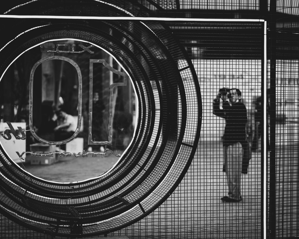 grayscale photo of man and woman standing in front of tunnel