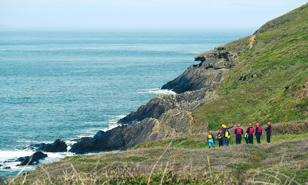 people hiking on rocky mountain near sea during daytime