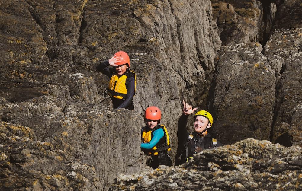 2 men climbing rocky mountain during daytime