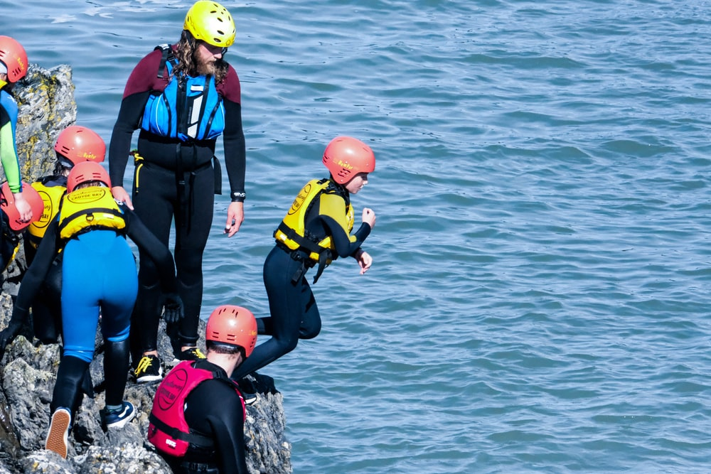 people in black and yellow wet suit wearing red helmet on black rock near body of with with with with