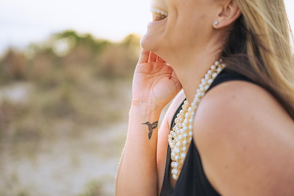 woman in black tank top wearing gold earrings
