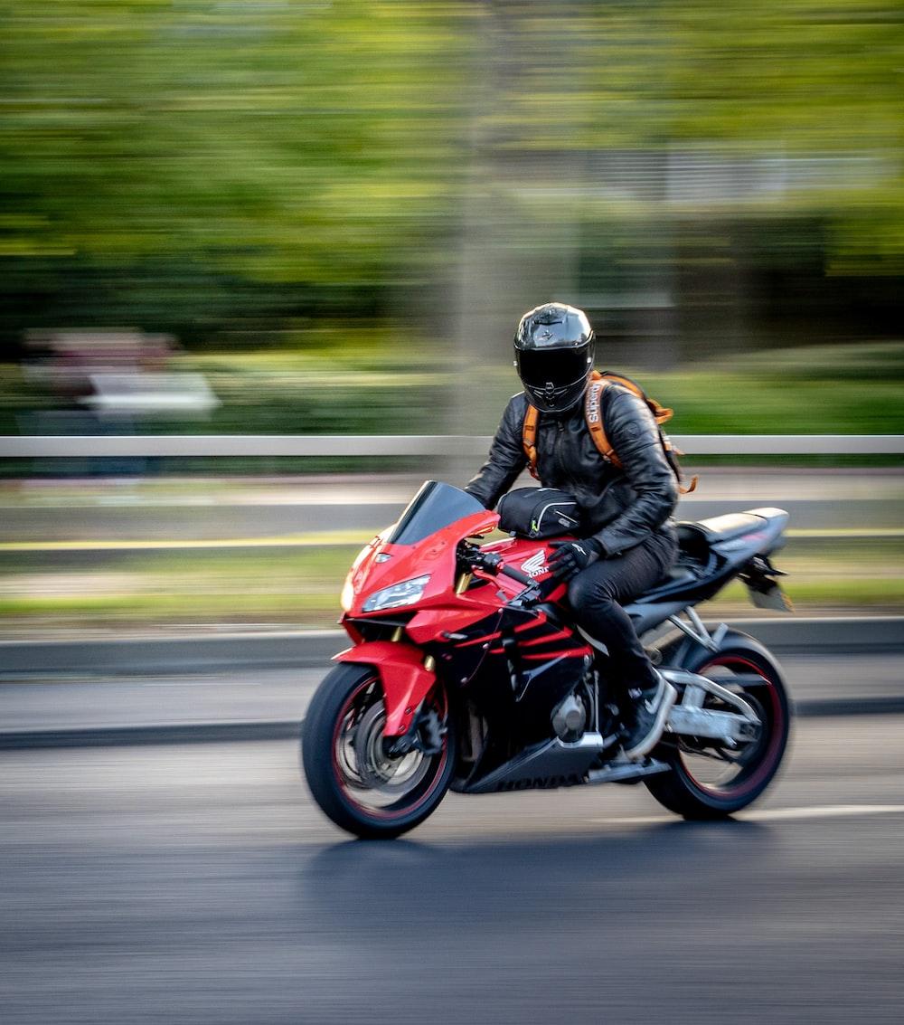 man in black helmet riding red sports bike