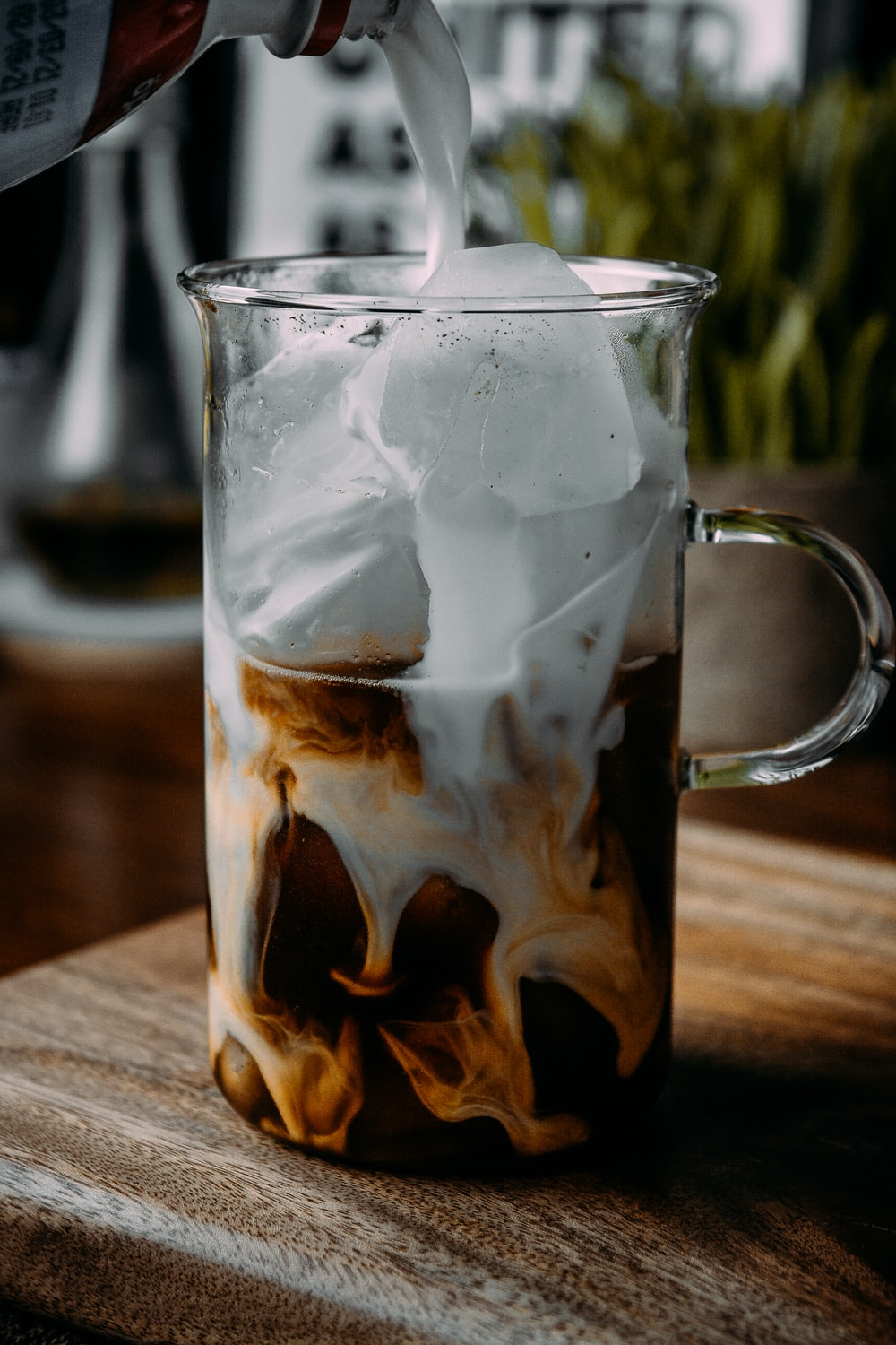 clear glass mug with ice cubes and brown liquid