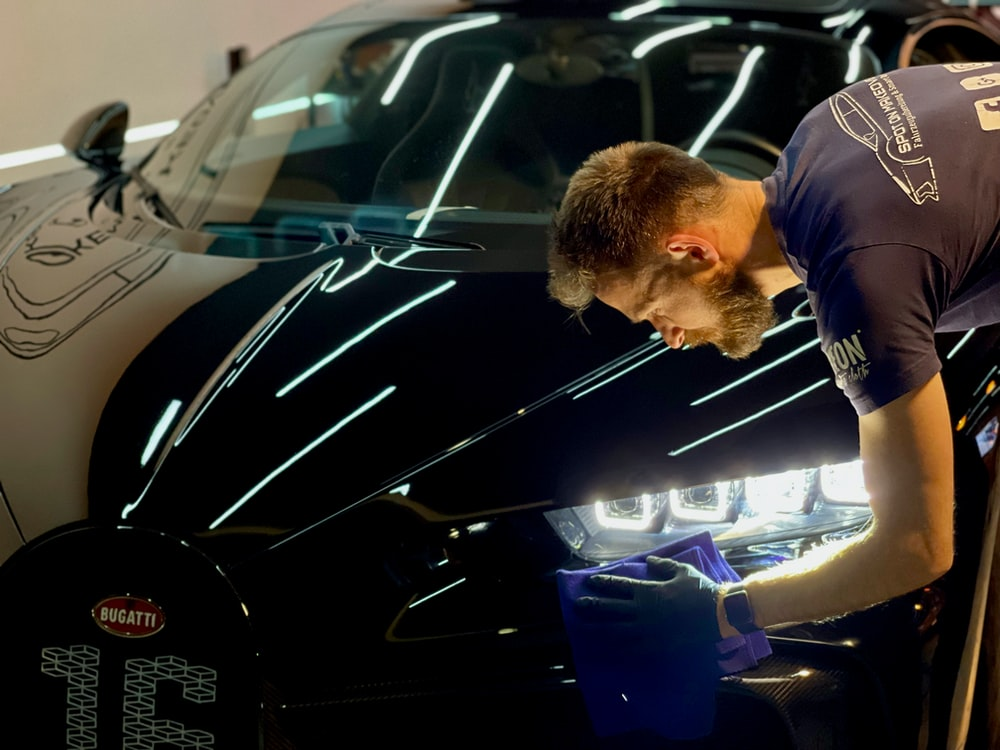 man in blue crew neck t-shirt standing beside black car