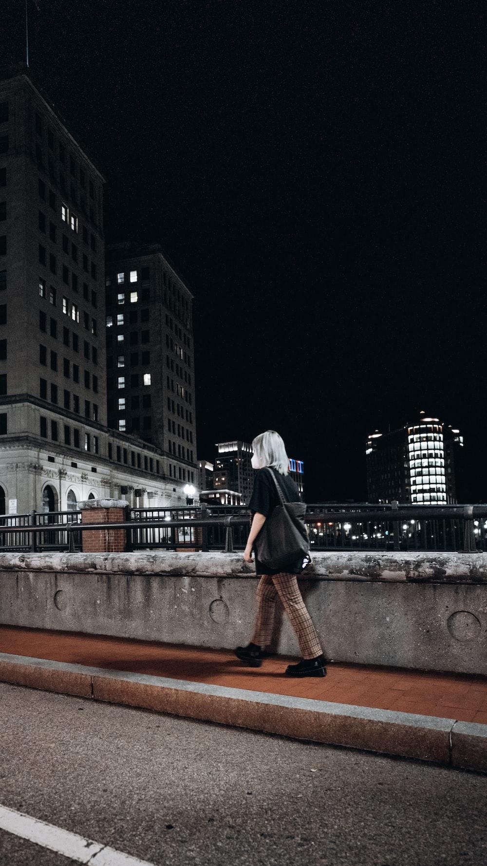 woman in black dress standing on brown concrete bridge during nighttime