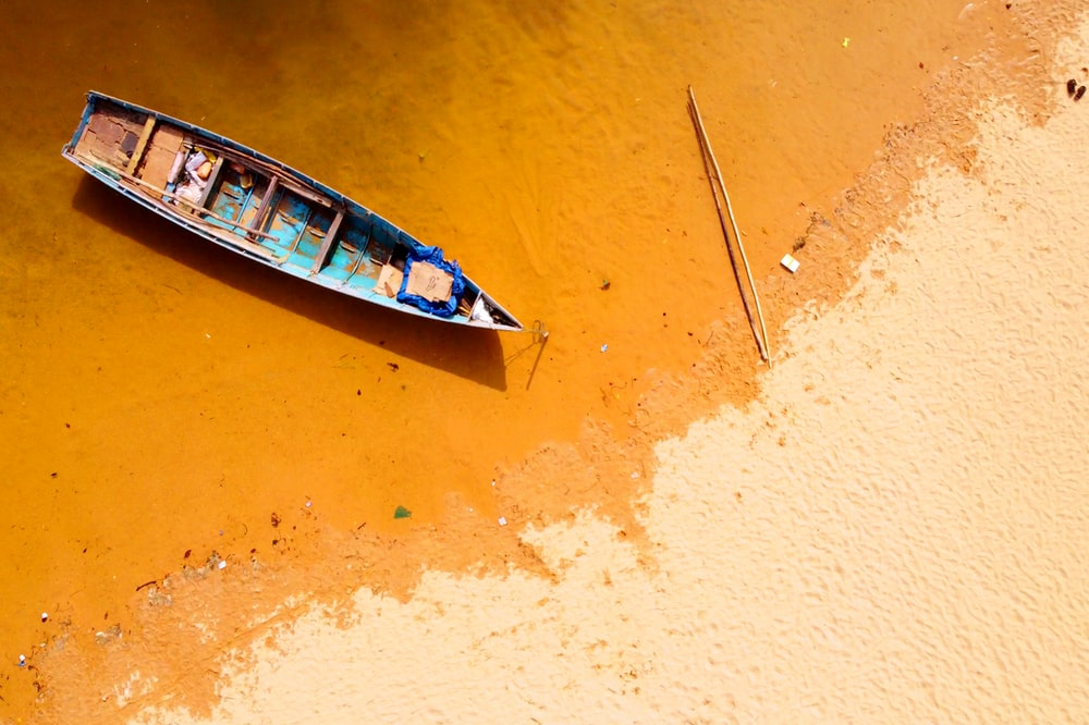white and blue boat on brown sand