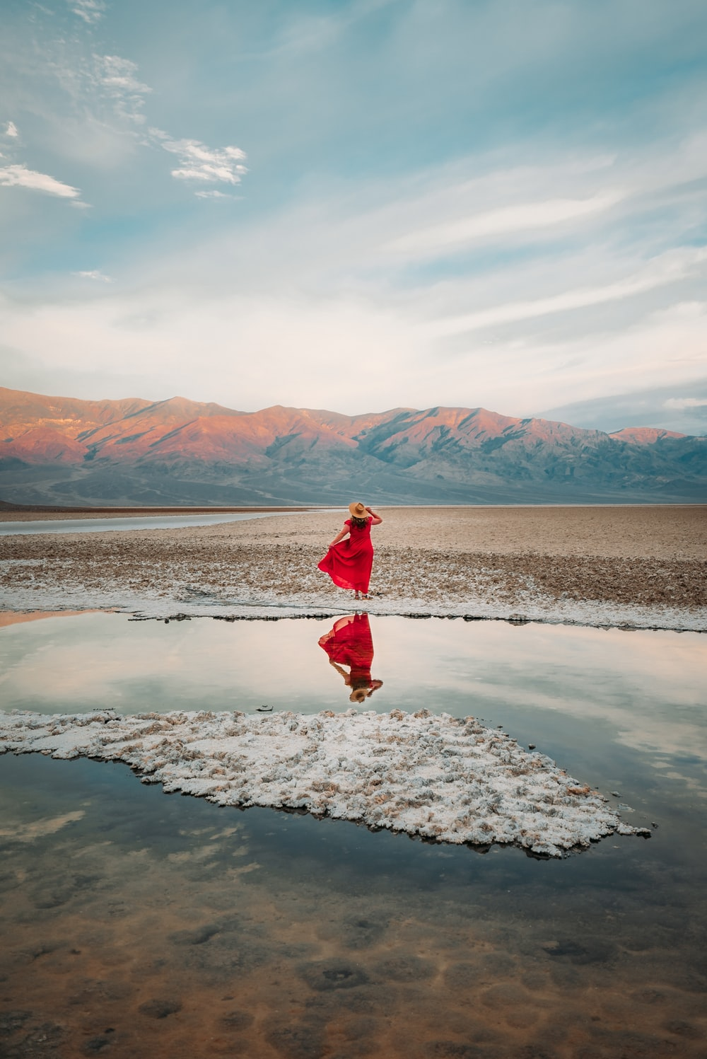 woman in red jacket standing on white snow covered ground during daytime