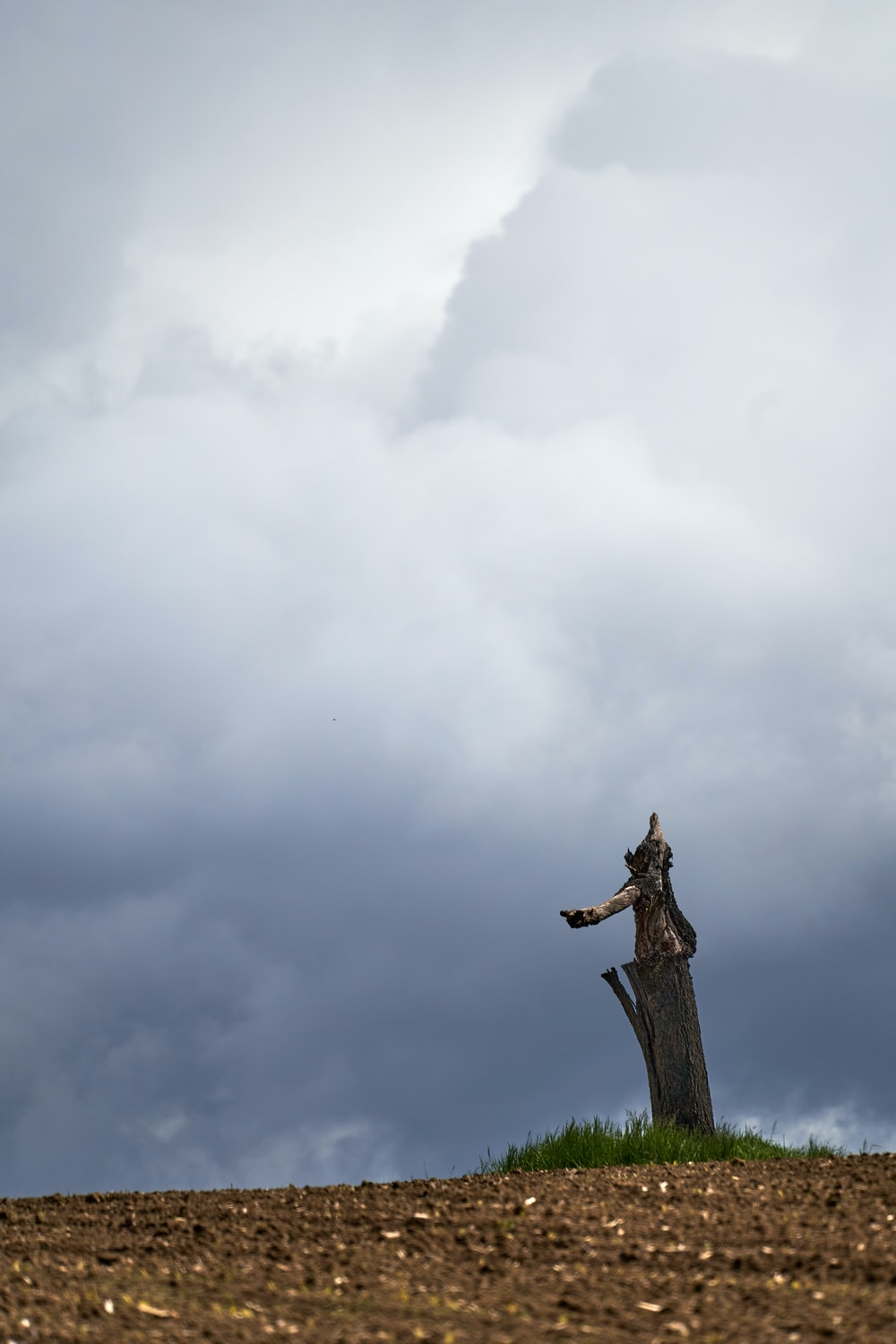 brown wooden cross under white clouds during daytime
