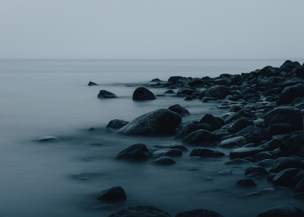 black rocks on body of water during daytime