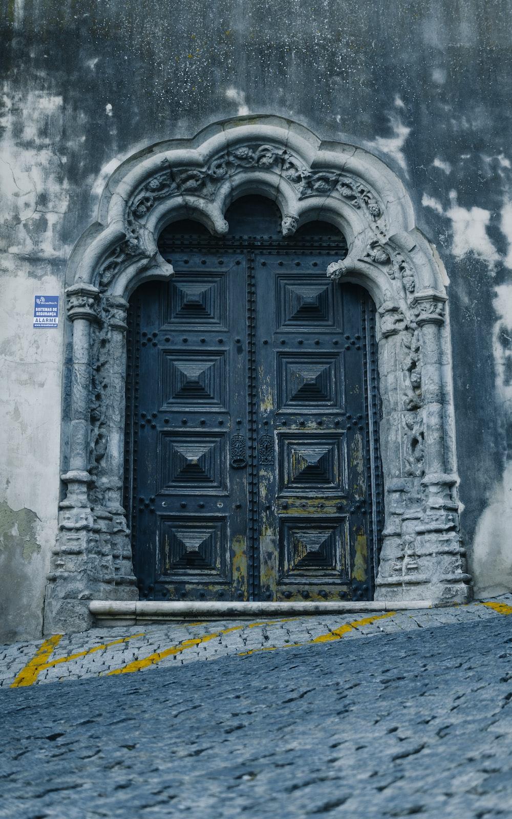 black wooden door on gray concrete wall