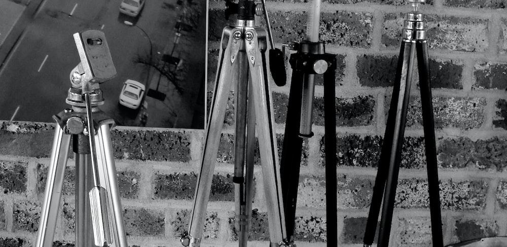 black camera tripod near white wall