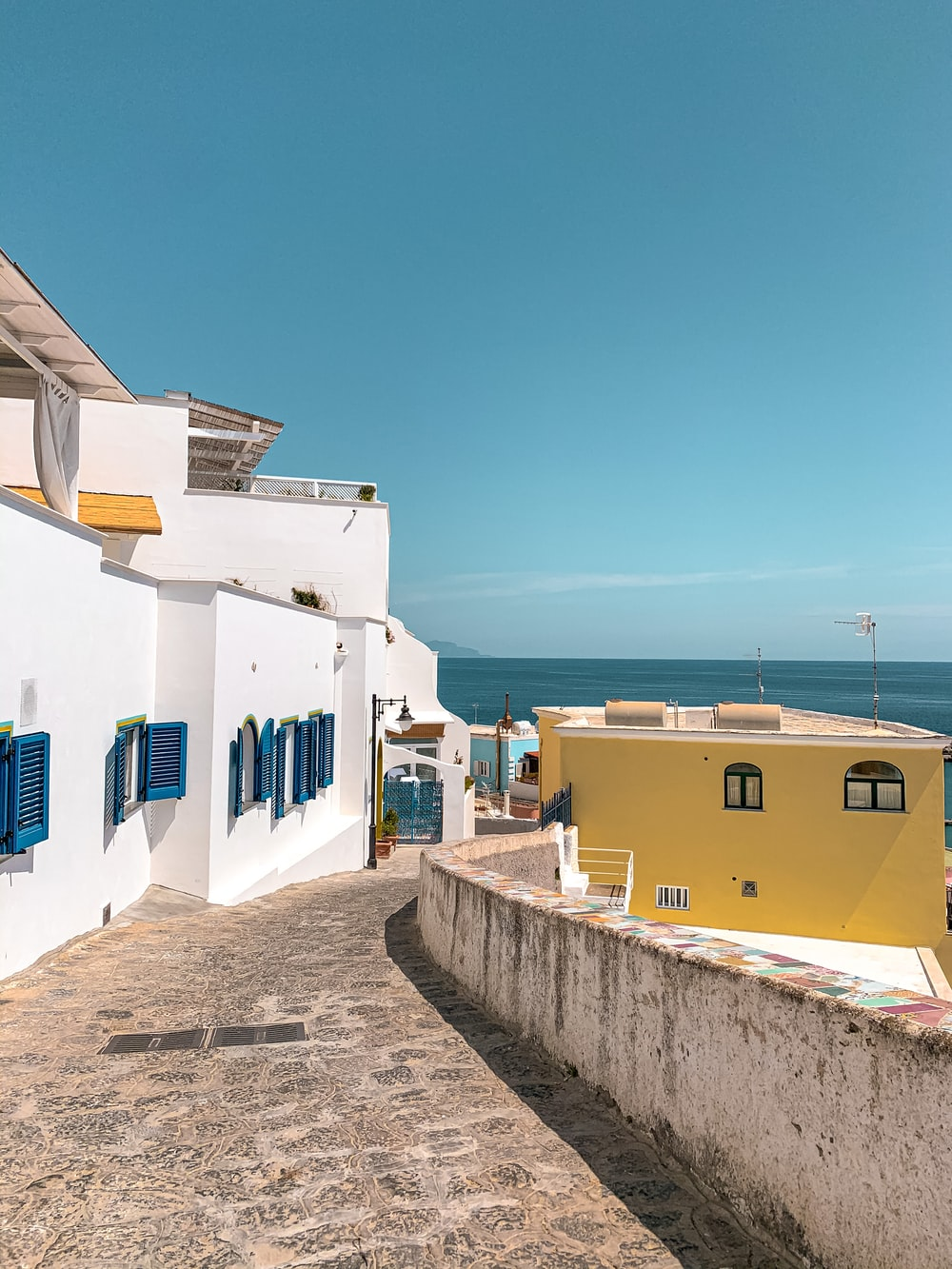 white and blue concrete houses near sea during daytime