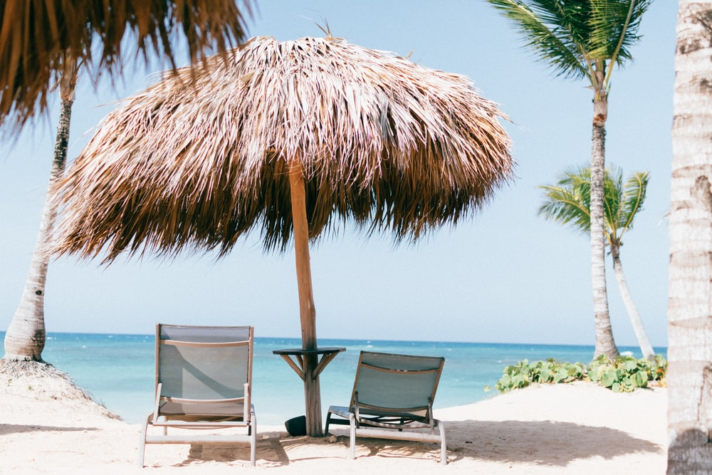 brown beach umbrella near white lounge chair under blue sky during daytime