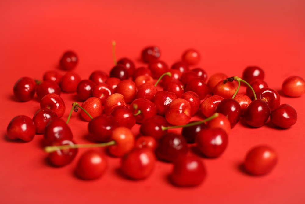 red cherry fruits on red surface