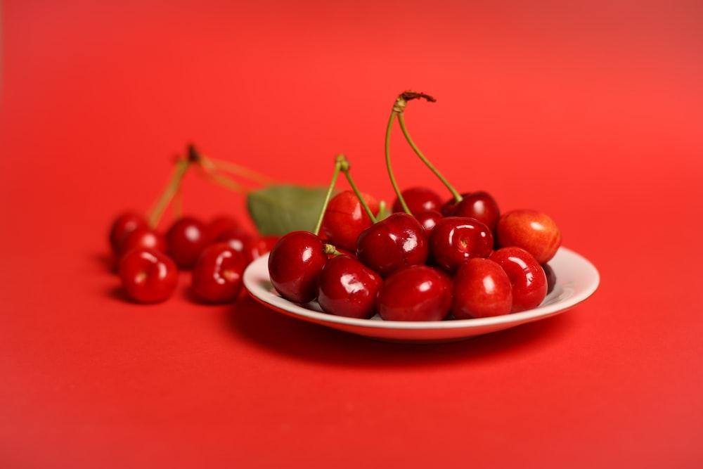 red cherry fruits on white ceramic bowl