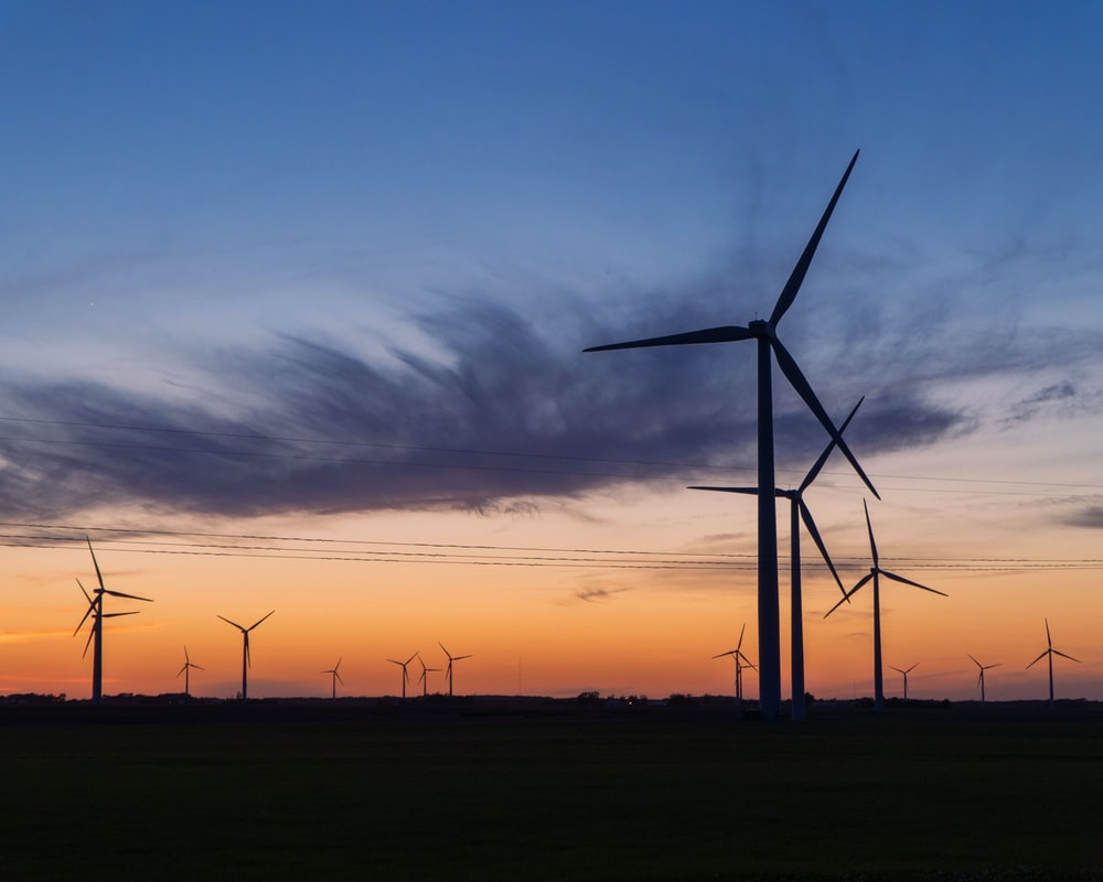 wind turbines under cloudy sky during sunset