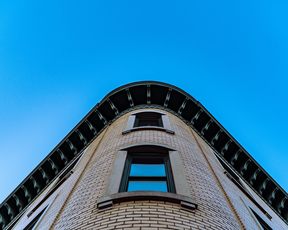 low angle photography of beige concrete building under blue sky during daytime