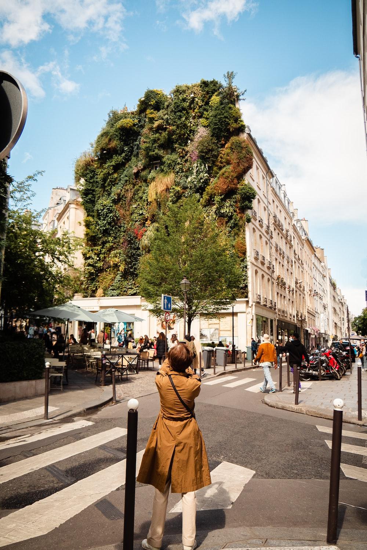 woman in brown jacket standing on sidewalk during daytime