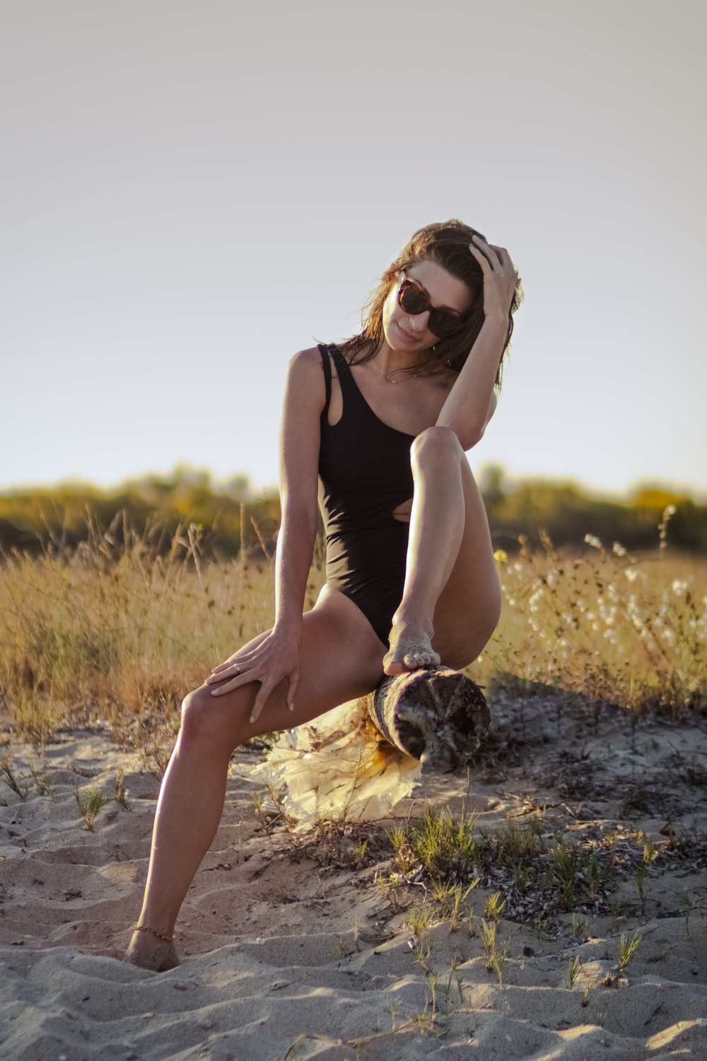woman in black tank top and brown skirt sitting on brown grass field during daytime