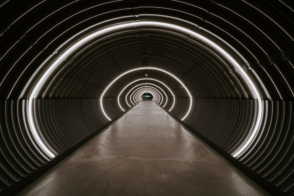 gray tunnel with light turned on during daytime