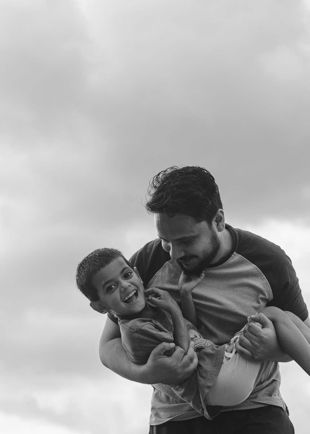 man in black long sleeve shirt carrying baby in gray scale